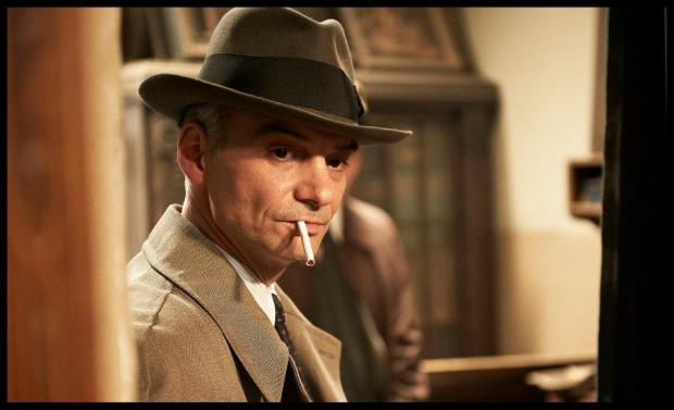"""מעיל גשם, מגבעת, סיגריה נצחית. בלי זה, החוקר לא יכול לחקור. מתוך """"מתוך הצללים""""."""