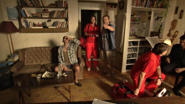 להטעין את הפלאפון...זה שם. השכן שותה לחיי המת. ושותה. ושותה. והפראמדיק מדבר עם הקברן ליד הגופה. מתוך הסרט.